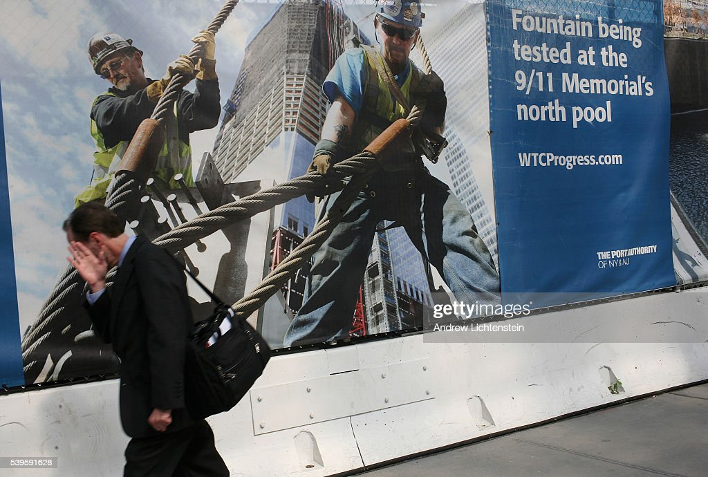 A businessman passes a poster paying tribute to construction workers on the edge of Ground Zero few of who could afford to live in the revitalized...