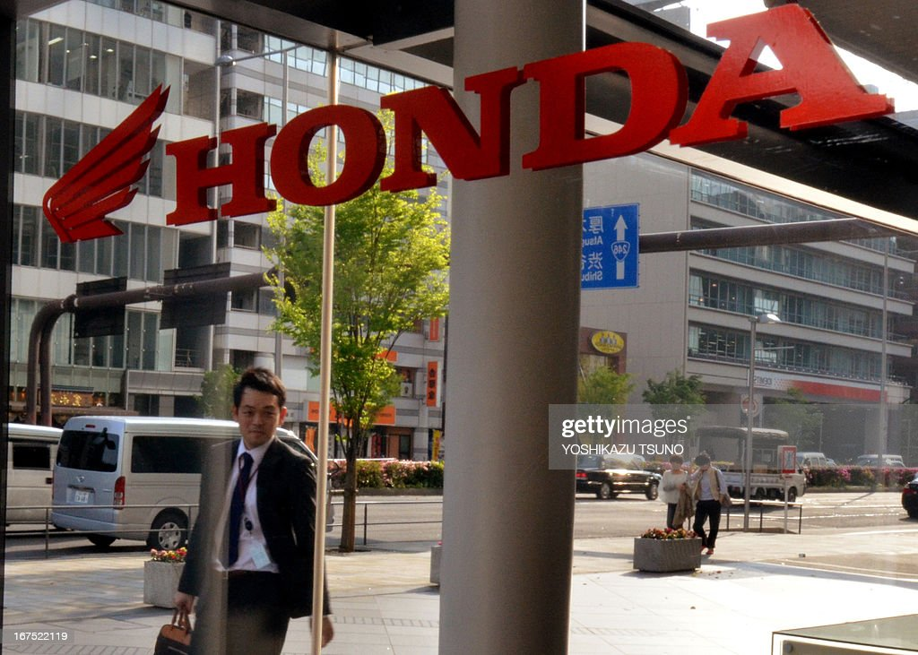 A businessman passes before a logo of Honda in Tokyo on April 26, 2013. Japanese automaker Honda said on April 26 its net profit for the year to March soared 73.6 percent to 3.7 billion USD, thanks to robust overseas sales, a weaker yen, and cost cutting. AFP PHOTO / Yoshikazu TSUNO