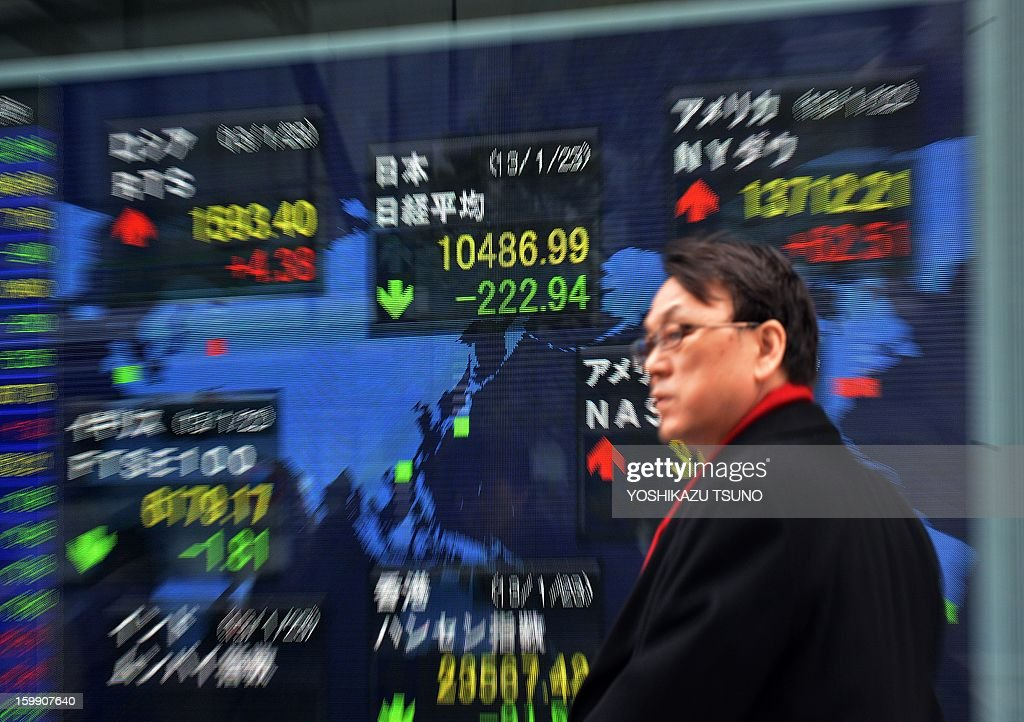 A businessman passes before a share prices board in Tokyo on January 23, 2013. Japan's share prices fell 222.94 points to close at the Tokyo Stock Exchange, extending losses from the previous day, as a lack of surprises in the the Bank of Japan's monetary policy announcement left dealers disappointed. AFP PHOTO / Yoshikazu TSUNO