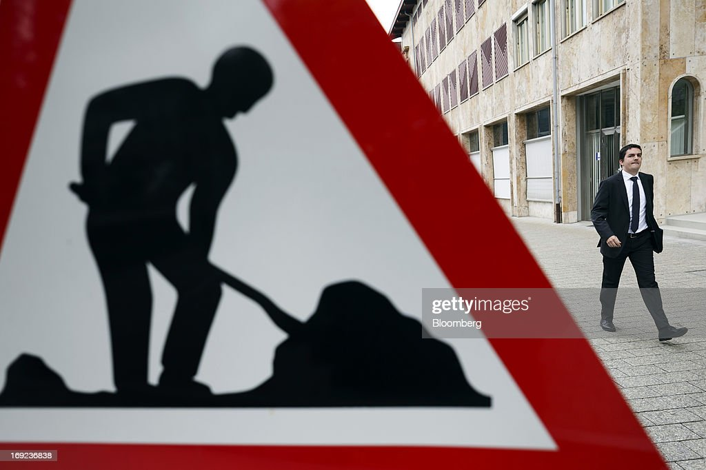 A businessman passes road maintenance sign near the Liechtenstein Museum of Fine Arts in Vaduz, Liechtenstein, on Tuesday, May 21, 2013. Liechtenstein, an alpine principality once fabled for its banking secrecy laws, remains a place favored by billionaires to stash the holding companies and investment entities that control their assets. Photographer: Valentin Flauraud/Bloomberg via Getty Images