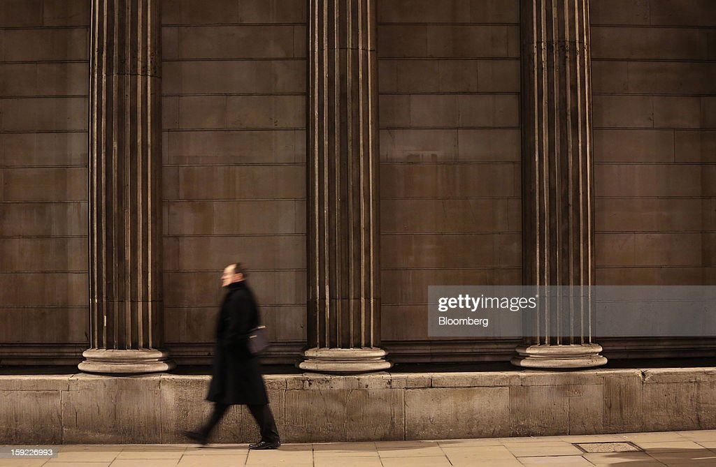 A businessman passes stone columns outside the Bank of England (BOE) in London, U.K., on Wednesday, Jan. 9, 2013. Bank of England policy makers will probably refrain from adding further stimulus to the U.K. economy today as their new credit-boosting program shows early signs of success. Photographer: Chris Ratcliffe/Bloomberg via Getty Images