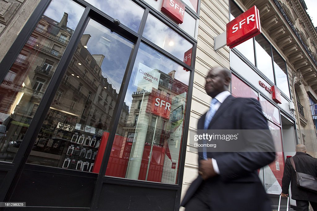 A businessman passes the window display of an SFR store, a mobile-phone unit of Vivendi SA, in Paris, France, on Thursday, Sept. 19, 2013. Bank of France General Council member Bernard Maris said France will end up restructuring its debt as tax 'optimization' by large companies including Google Inc. will leave too big a burden on the middle class. Photographer: Balint Porneczi/Bloomberg via Getty Images