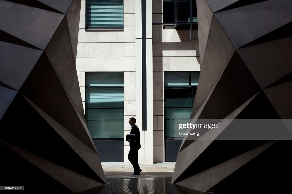 A businessman passes through Bishop's Court past two sculptural air vents, designed by Heatherwick Studios, in the financial district of London, U.K., on Friday, Aug. 17, 2012. Banks, insurers and other financial-services firms may eliminate a total of about 3,000 jobs across greater London as companies in the New York region add 9,000, according to U.K.-based researcher Oxford Economics Ltd. Photographer: Simon Dawson/Bloomberg via Getty Images