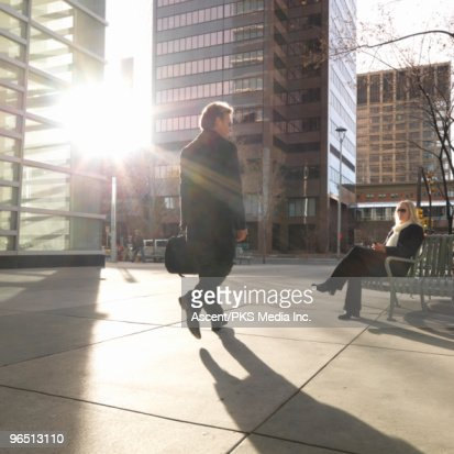Businessman passes woman waiting on city bench : Stock Photo