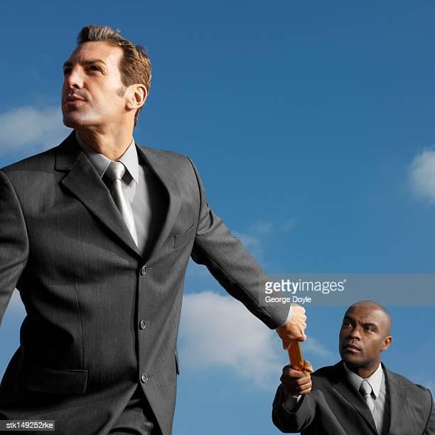 businessman passing baton to businessman, low angle view