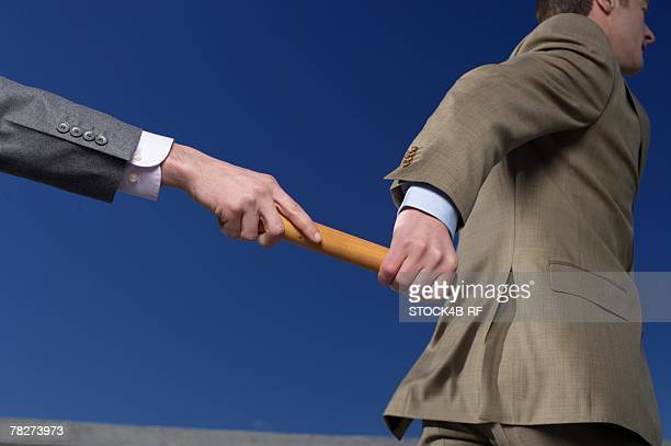 Businessman passing baton to colleague