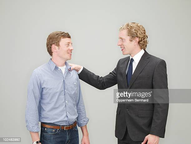 businessman patting a man on the shoulder