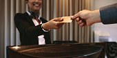 Close up of businessman paying with credit card at reception desk in hotel. Business man giving credit card to hotel receptionist for payment of his room. Focus on hands.