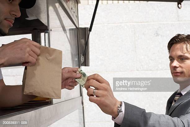 Businessman paying street food cart vendor
