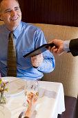 Geschäftsmann hält bill im restaurant.