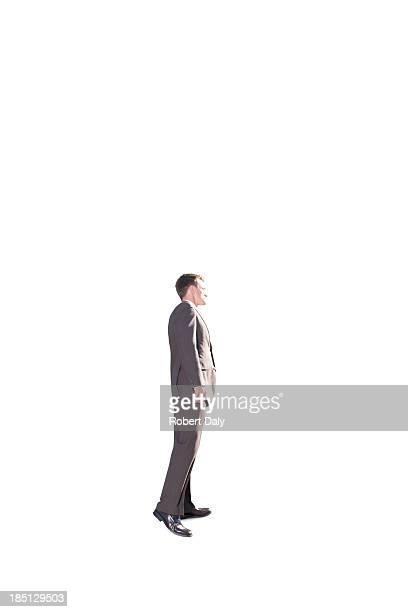 A businessman peeking around the corner