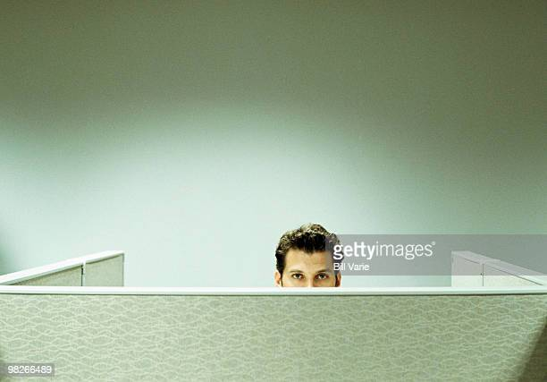 Businessman peeking over cubicle wall