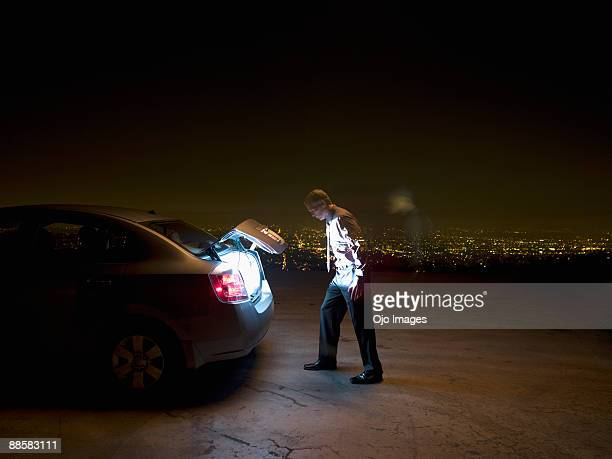 Businessman peering into open glowing car trunk