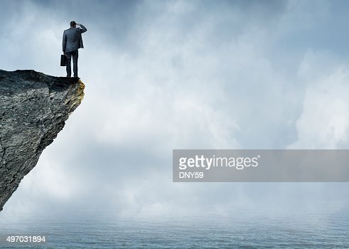 Businessman Peering Out To Sea