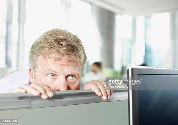Uomo d'affari sulla parete Sbirciare cabina