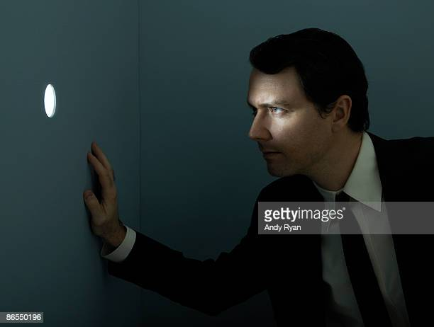 Businessman peering through illuminated peep hole.