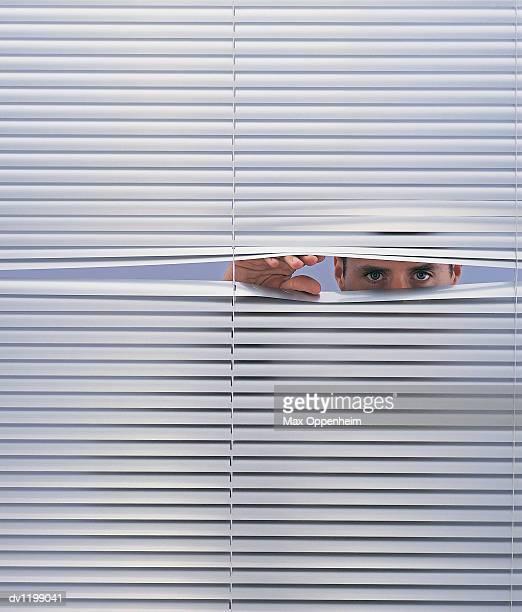 Businessman Peering Through Venetian Blinds