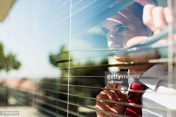 Businessman peering through window blinds