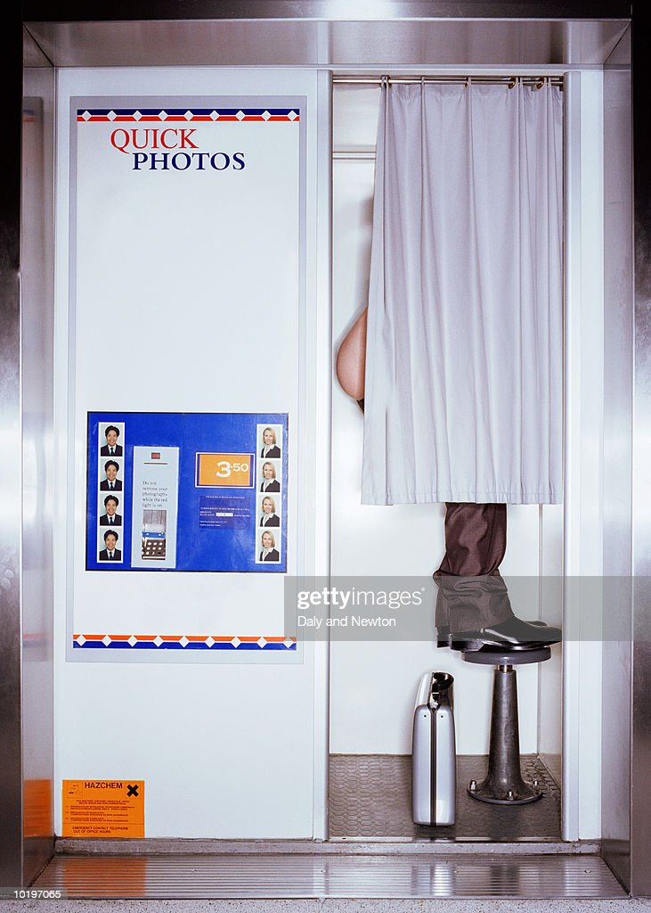 Businessman photographing bottom in booth : Stock Photo