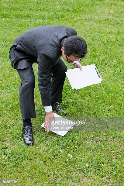 Businessman picking up paperwork outdoors