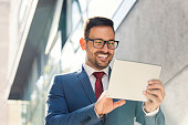 Smiling young businessman using tablet in front of the office