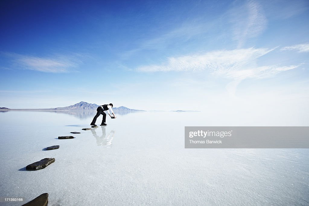 Businessman placing next stone in pathway in lake