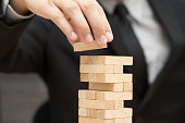 Businessman placing wooden block on a tower. Risk and strategy in business concept