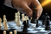 Businessman play chess use King - Chess Piece white to crash overthrow the competitor concept business strategy for win