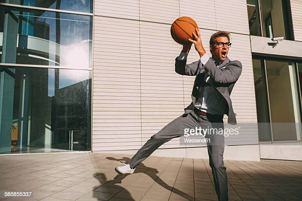 Businessman playing basketball outdoors