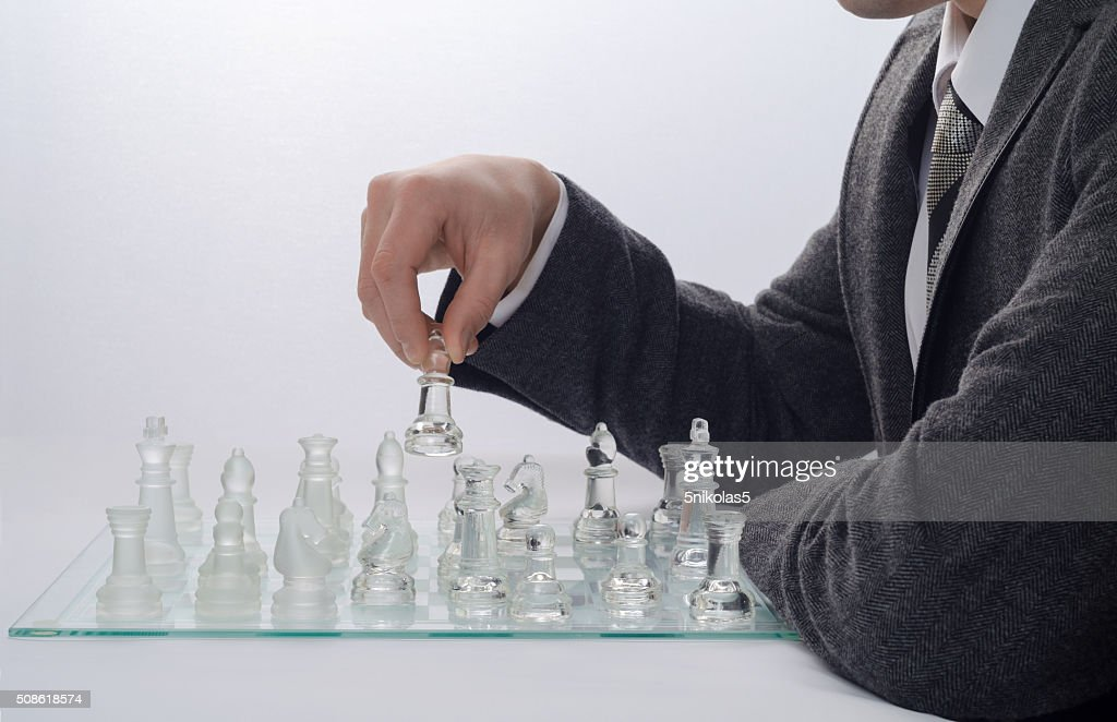 businessman playing chess on a light background : Stock Photo