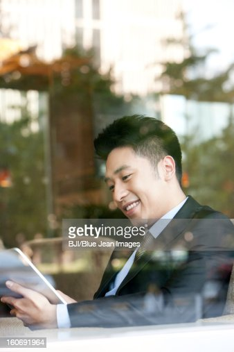 Businessman playing digital tablet in cafe : Stock Photo