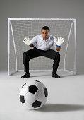 Businessman playing goalkeeper, ready to block the ball, studio shot