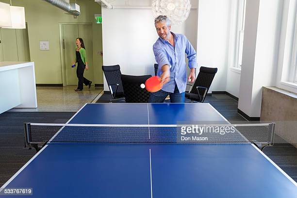 Businessman playing table tennis in office