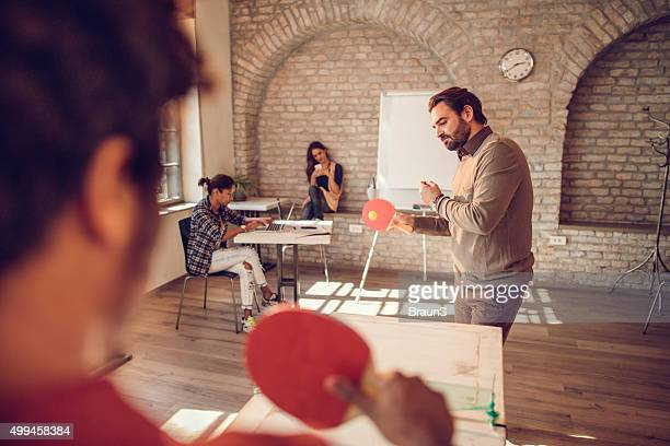 Businessman playing table tennis with his colleague at casual office.