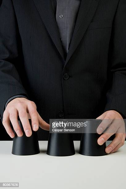 A businessman playing the shell game