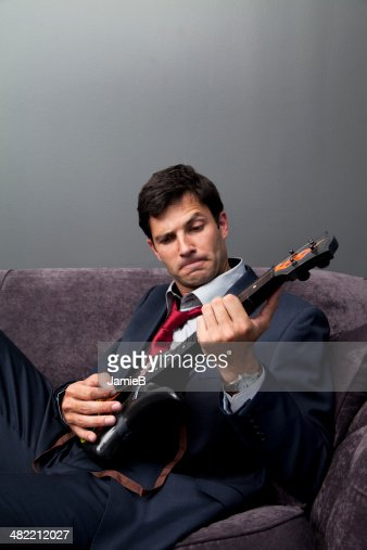 Businessman playing toy guitar : Stock Photo