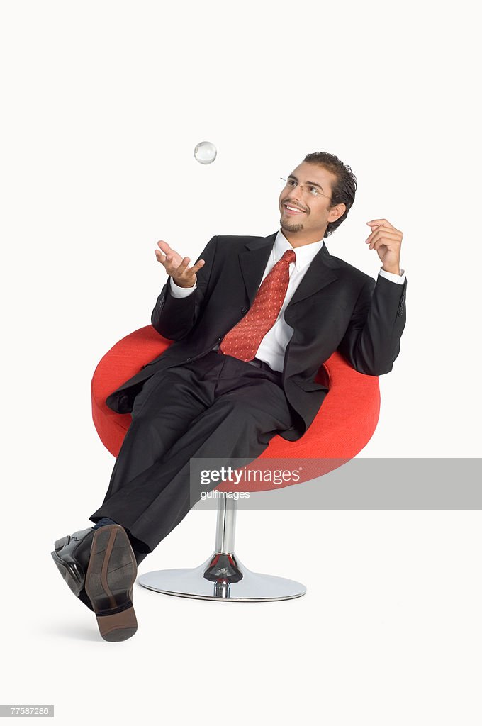 Businessman playing with paperweight, smiling : Stock Photo
