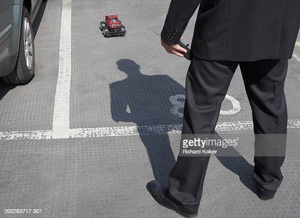 Businessman playing with radio controlled car, outdoors, low section