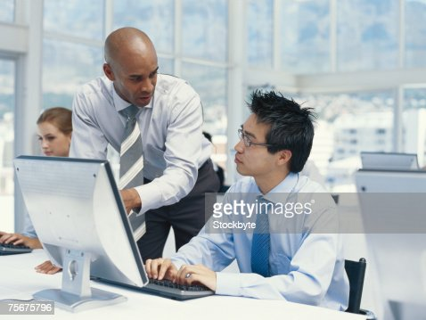 Businessman pointing at computer monitor and explaining to man : Stock Photo