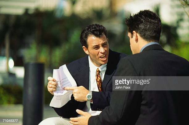Businessman pointing at document and arguing