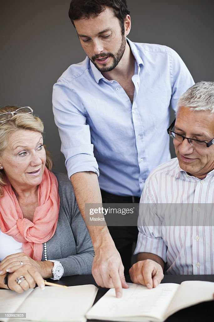 Businessman pointing at document in meeting : Stock Photo