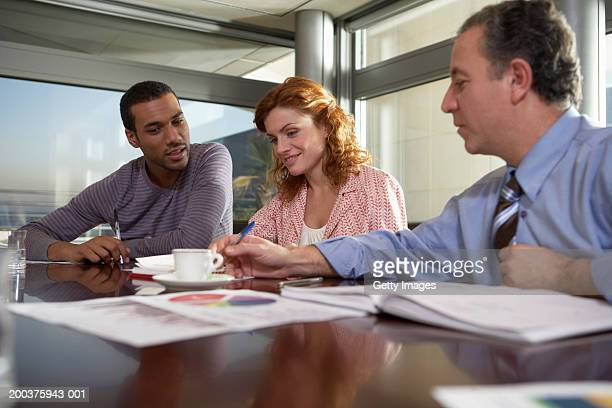Businessman pointing at paperwork in meeting with colleagues