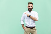 Businessman pointing copy space. Handsome young adult man with beard in white shirt looking at camera and pointing away while standing isolated on white background