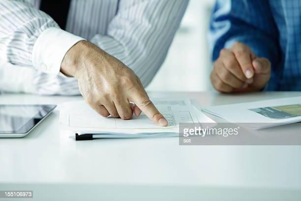 Businessman pointing finger at plans