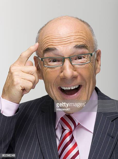 Businessman pointing finger towards head, portrait, close-up