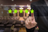 Businessman pointing five star symbol to increase rating of hotel over Abstract blurred photo of conference hall or seminar room with attendee background, business evaluation concept, Increase rating