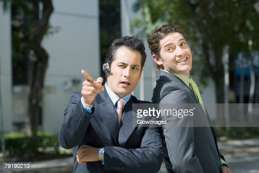Businessman pointing forward with another businessman standing beside him : Foto de stock