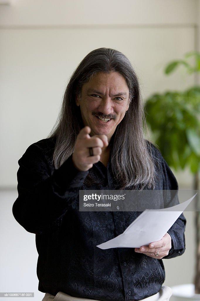 Businessman pointing, smiling, portrait : Stock Photo