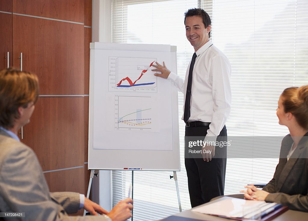 Businessman pointing to flipchart in conference room : Stock Photo