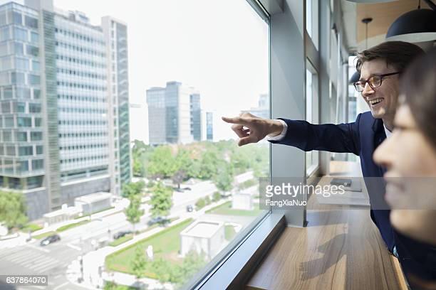 Businessman pointing to scene through window